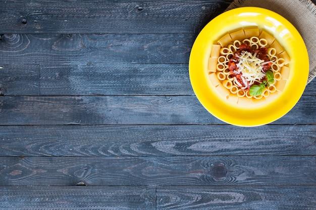 Vista superior do rigatoni de massa italiana com molho à bolonhesa, sobre um fundo de madeira rústico