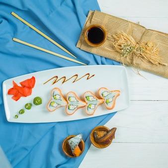 Vista superior do rolo de sushi tradicional da filadélfia de culinária japonesa com salmão abacate de pepino de queijo da filadélfia, disposto em forma de coração no backgrou branco e azul