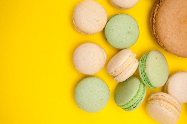 Vista superior do sabor do macaroon de caramelo grande ao lado de pequenos biscoitos sobre fundo amarelo. desset sortido