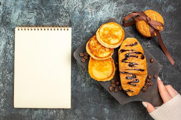 Vista superior do saboroso café da manhã com panquecas, croisasant, biscoitos empilhados e caderno na superfície escura