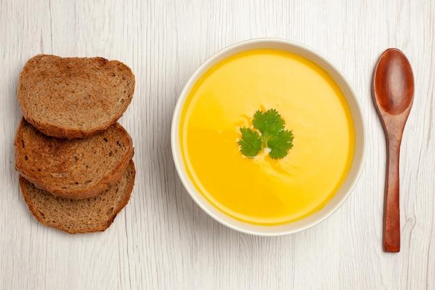 Vista superior do saboroso creme de sopa de abóbora texturizado com pão escuro em branco