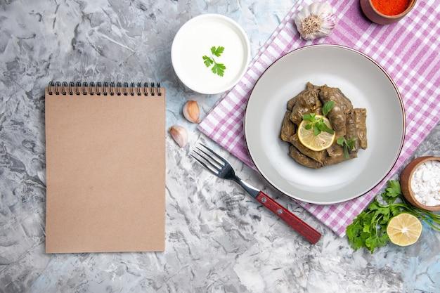 Vista superior do saboroso dolma de folhas dentro do prato na superfície branca