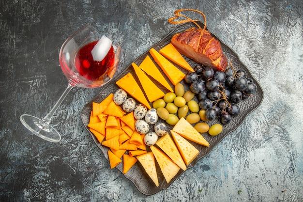 Vista superior do saboroso lanche em uma bandeja marrom e uma taça de vinho caída no fundo de gelo