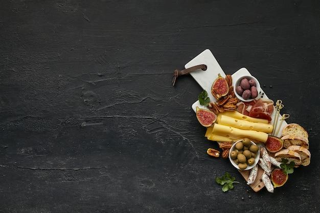 Vista superior do saboroso prato de queijo com frutas, uvas, nozes, azeitonas e pão torrado na mesa preta.