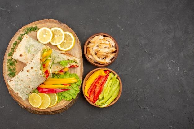 Vista superior do saboroso sanduíche de carne fatiada de shaurma com rodelas de limão no preto