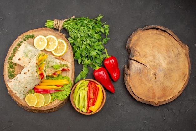 Vista superior do saboroso sanduíche de frango fatiado shaurma com limão e verduras no escuro