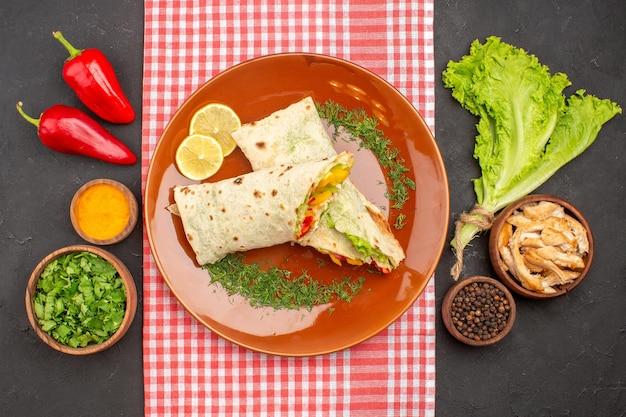 Vista superior do saboroso sanduíche de salada shaurma fatiada com verduras e salada no escuro