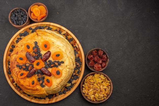 Vista superior do saboroso shakh plov cozido arroz dentro de uma massa redonda com passas na superfície cinza