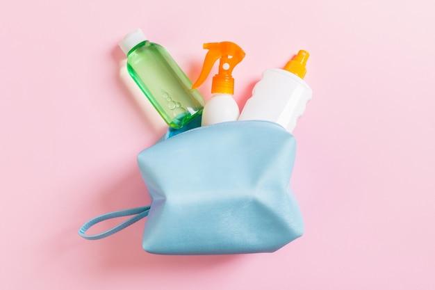 Vista superior do saco de cosméticos feminino cheio de spray de suncream, protetor solar, protetor solar e loção para o corpo e creme de spf em fundo rosa com espaço de cópia. diretamente acima. conceito de verão brilhante