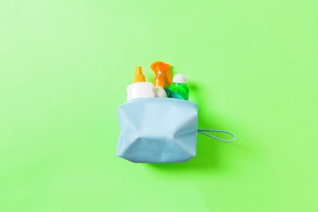 Vista superior do saco de cosméticos femininos cheio de protetor solar, protetor solar, protetor solar e loção corporal e creme fps em fundo verde com espaço de cópia. diretamente acima. conceito de verão brilhante.