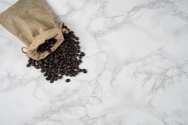 Vista superior do saco de grãos de café torrado sobre a superfície de mármore branco com copyspace