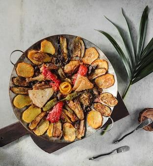 Vista superior do saj kebap com costelas de cordeiro batatas pimentões coloridos e berinjelas em uma placa de madeira em cima da mesa