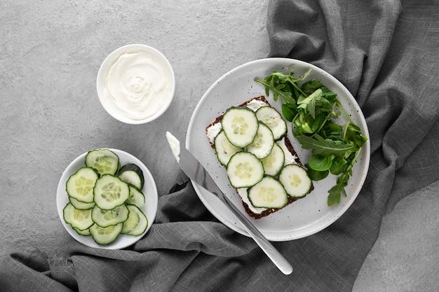 Vista superior do sanduíche com pepinos no prato e faca