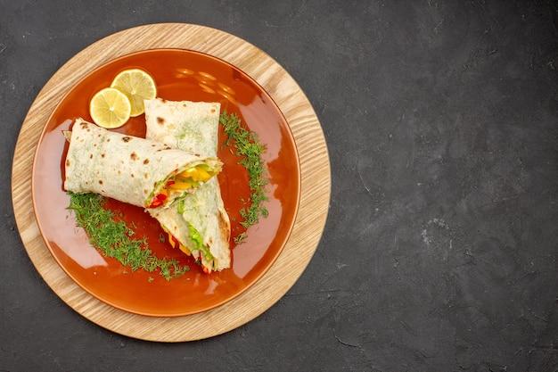 Vista superior do sanduíche de carne deliciosa shaurma fatiado dentro de uma placa marrom no preto