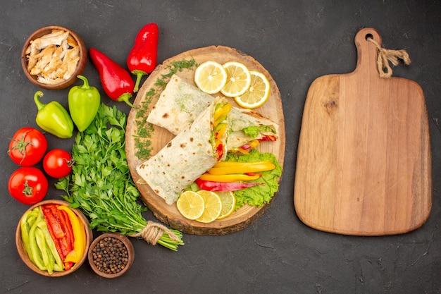 Vista superior do sanduíche de carne shaurma fatiada com limão e verduras no preto