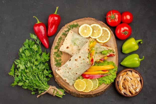 Vista superior do sanduíche de carne shaurma fatiada com rodelas de limão e verduras no preto
