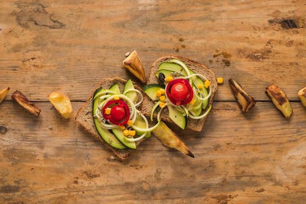 Vista superior do sanduíche de legumes com fatia de batata assada na mesa de madeira