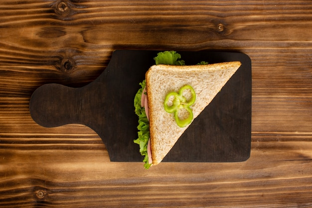 Vista superior do sanduíche delicius com salada verde e presunto na superfície de madeira