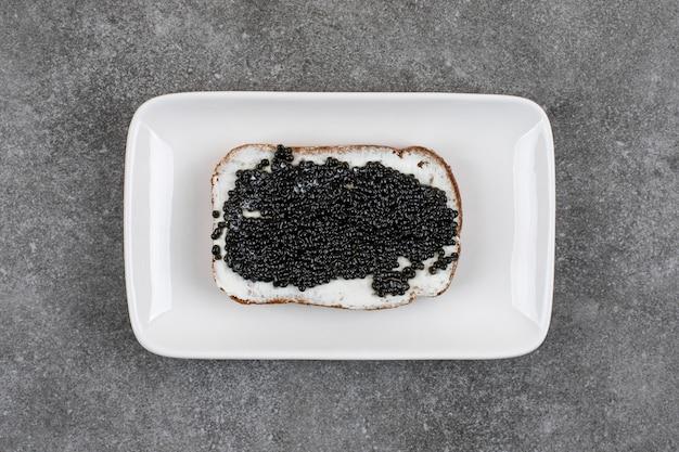 Vista superior do sanduíche fresco com caviar preto.