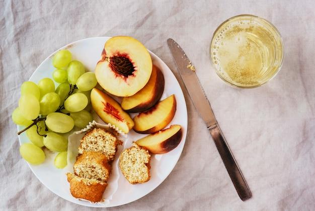 Vista superior do saudável brunch refrescante com frutas e copo de vinho branco sobre o pano de mesa