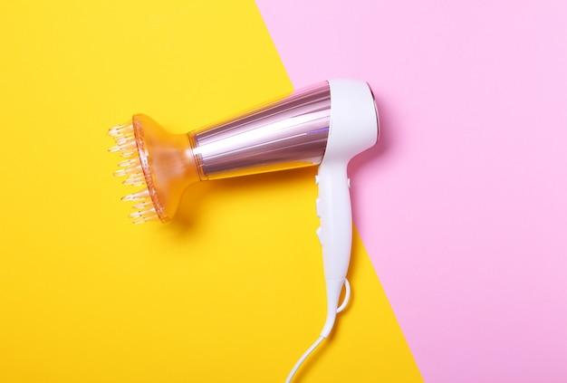 Vista superior do secador de cabelo branco e rosa em amarelo e rosa. lay plana, minimalismo. conceito de cuidados com o cabelo. secador de cabelo iônico metálico rosado. ferramenta de estilo de cabelo profissional.