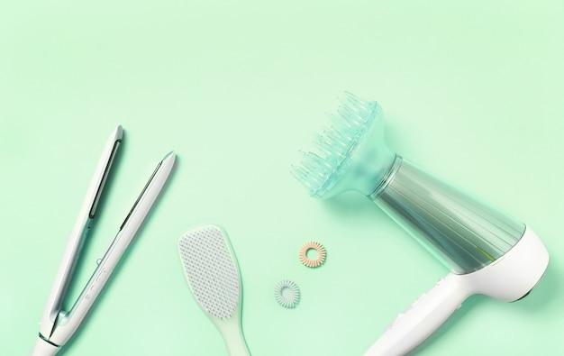 Vista superior do secador de cabelo, ferro de alisar, escova de cabelo e acessórios na hortelã. lay plana, conceito de cuidados do cabelo. ferramenta de estilo de cabelo profissional.