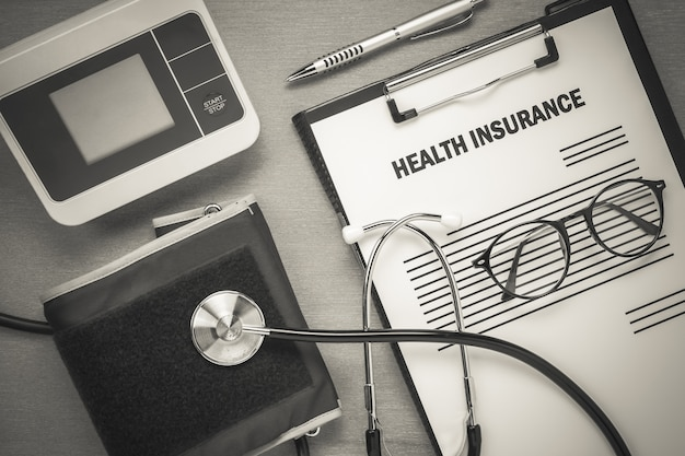 Vista superior do seguro de saúde formam óculos e medidor de pulso com estetoscópio em fundo de madeira.