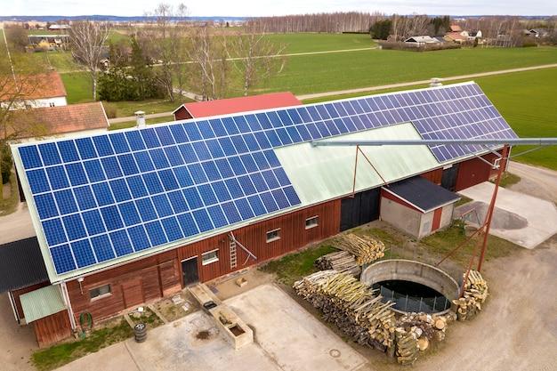 Vista superior do sistema solar azul dos painéis voltaicos da foto no telhado de madeira da construção, do celeiro ou da casa. conceito de produção de energia verde ecológica renovável.