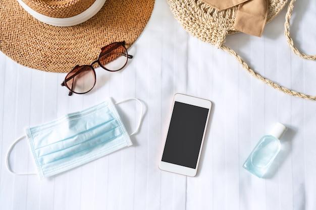 Vista superior do smartphone, acessórios de viagem, máscara cirúrgica e gel desinfetante na cama em quarto de hotel