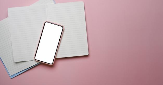 Vista superior do smartphone com tela em branco, caderno vazio e espaço de cópia