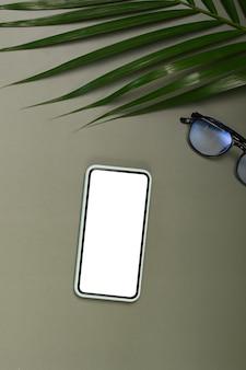 Vista superior do smartphone e óculos na mesa