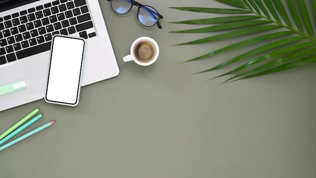 Vista superior do smartphone, laptop, acessórios e suprimentos na mesa