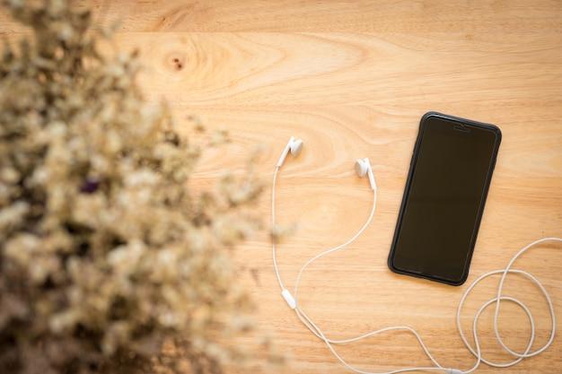 Vista superior do smartphone preto, fone de ouvido no fundo de madeira rústico.