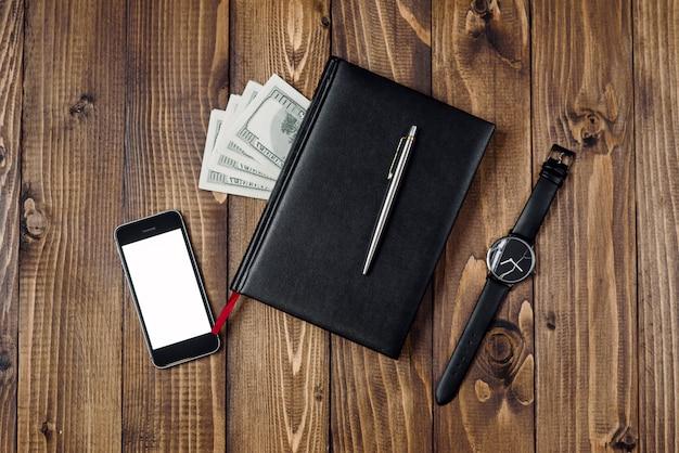 Vista superior do smartphone, relógio, caneta, caderno e dinheiro
