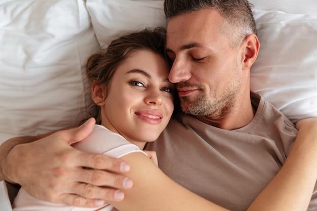 Vista superior do sorridente casal apaixonado, deitado juntos na cama em casa