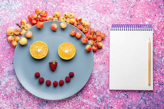 Vista superior do sorriso de frutas dentro do prato com o bloco de notas na mesa rosa brilhante