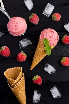 Vista superior do sorvete de morango em um cone de waffle no fundo preto.