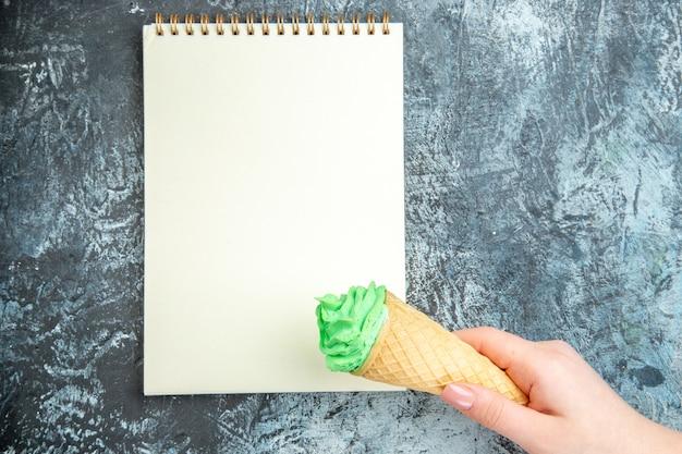 Vista superior do sorvete na mão de uma mulher com um caderno em um fundo escuro.