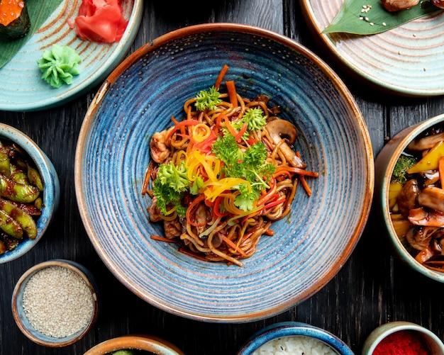 Vista superior do stir frito macarrão com legumes e camarão em um prato na mesa de madeira