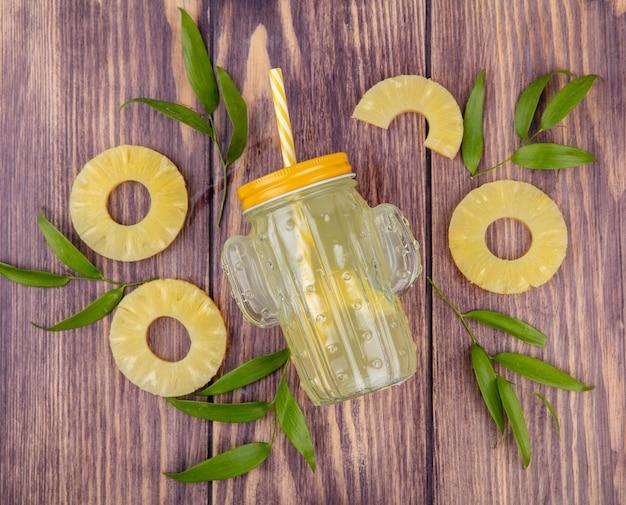 Vista superior do suco de abacaxi com fatias de abacaxi e folhas na superfície de madeira