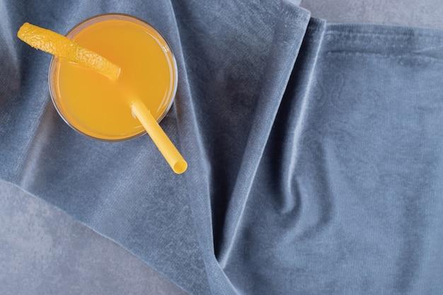Vista superior do suco de laranja acabado de fazer em fundo cinza.