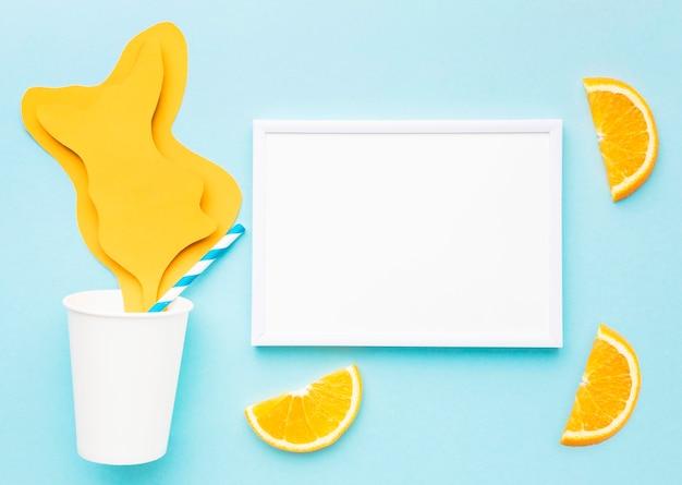 Vista superior do suco de papel derramado com fatias de laranja e moldura
