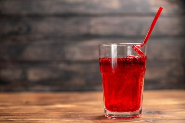 Vista superior do suco natural de groselha fresca em um copo servido com um tubo no lado esquerdo em uma mesa de madeira