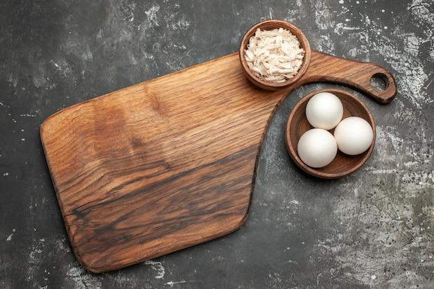 Vista superior do suporte de prato com uma tigela de queijo e uma tigela de ovos ao lado na mesa cinza escuro