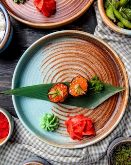 Vista superior do sushi japonês clássico com caviar vermelho na folha de bambu, servido com molho de gengibre e wasabi em um prato