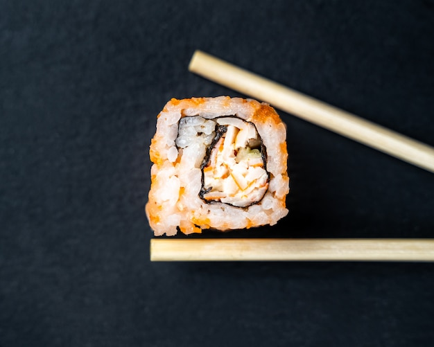 Vista superior do sushi uramaki servido na ardósia de pedra.