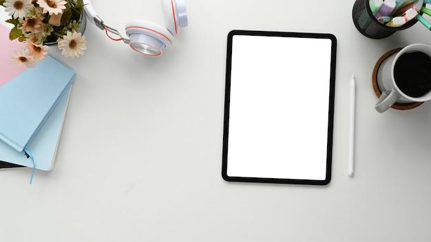 Vista superior do tablet, caderno, xícara de café e fone de ouvido na mesa branca