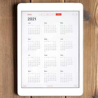 Vista superior do tablet com calendário aberto para 2021 anos em uma mesa de tábuas de madeira