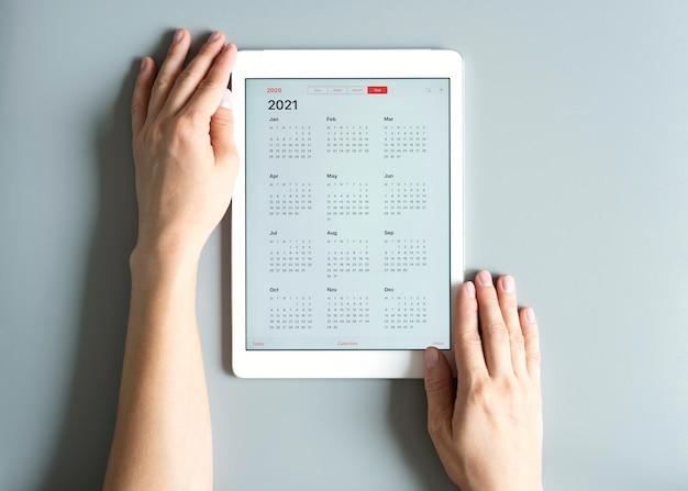 Vista superior do tablet com calendário aberto para 2021 anos em uma mulher com as mãos em cinza
