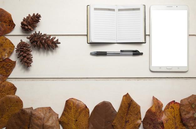 Vista superior do tablet com tela vazia e caderno no fundo da mesa branca, design plano leigo